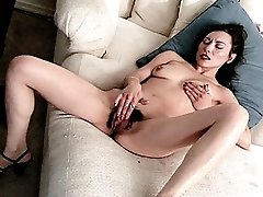 Asian slut rubbing her hairy honeypot on the couch