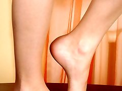 Sexy chick dances tiptoes on the table flashing her perfect nyloned feet