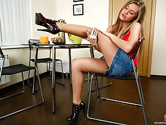 Vivacious chick mounts a table revealing her yummy feet in sheer pantyhose