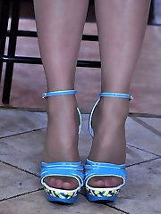 Frolic dark-haired displays her nyloned feet in and out of blue strappy sandals