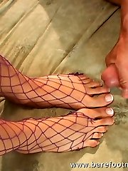 Fishnet brunette plays with pussy while getting her feet tongued