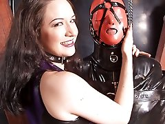 Two merciless mistresses keep their latex slave in bondage and teach him