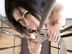 Ashley Renee is caged and corded by leather restrain bondage straps. The dame in distress fights against the metal device around her neck and her body is made immobile by the straps.