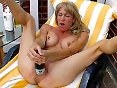 Kinky blonde fisting and fucking her cunt with a beer bottle