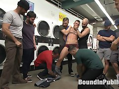 With his music blasting too loud, Tyler Rush acts like an obnoxious little fuck in the laundromat, pulling people's clothes out the dryer like he owns the place. The other clientele decide to step in and teach the boy a lesson in proper etiquette. They capture Tyler and call in their buddies to help adjust his attitude. Soon, Tyler is stripped, bound and groped on his knees, made to gag on a long row of dicks. Onlookers snap photos of the cocksucker as the owner Rocco Steele busts in. He can't stand the little prick just as much the other guys and joins the torment, fingering and spanking Tyler's ass. The dudes take turns spitroasting and slapping Tyler as he's secured to a laundry cart. Tyler takes multiple hot loads on his face as Rocco pounds his ass with an impossibly large cock. Unfortunately for Tyler, the lesson doesn't end there...