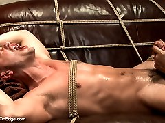 Adam Knox is a shy stud coming in for a standard photo shoot. When he sees some ropes lying around from a previous appointment his curiosity gets the best of him and he asks to be tied up. He continues posing in the ropes and doesn't stop the photographer from playing with his cock. But being brought to the edge of cumming the once shy Adam gets pissed off and demands to cum. This cocky stud is suspended in the air and the photographer fucks Adam's ass with a dildo and makes him beg in mid air. Finally, tied to the couch and blindfolded, Adam shoots a fat load all over himself. Shooting further than he ever has before.