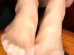 Kinky chick going wild while squashing faux-cock with her pantyhose clad feet