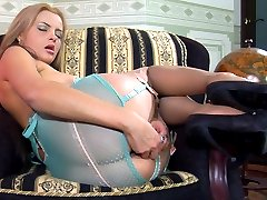 Busty sexpot plays with a sex toy exposing bow trimmed straps of her nylons