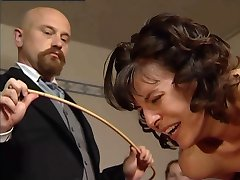 Pretty girl restrained over a desk to get a brutal caning on her bared ass