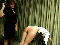 She pulls one of the school girls across her knee and gives her a bare handed spanking, as her accomplice watches. Mistress raises the girls skirt and spanks harder.