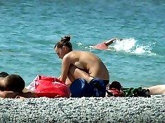 Topless beach chick pulls down her tiny black panties