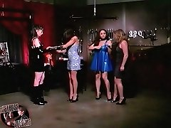 Strict dominas teach two female slaves in bondage lashing their round asses