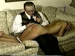 A bespectacled fellow takes out after a girl in little clothing who is ready but not willing to get spanked