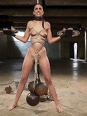 We welcome our bad gal Lyla Storm back for a second wearisome day in the dungeon space.  She is to be tested for endurance, resolve, and knowledge of the rules. She will do this with trays strapped to her hands, thick metal weights pulling her down. She proves willing to sweat thru her ordeal, but makes a serious misstep. She offers a lazy answer.