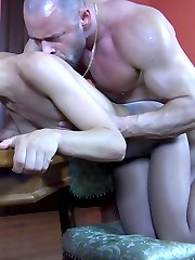 Half-naked babe mounts a table for some foot-worshipping and nylon bonking