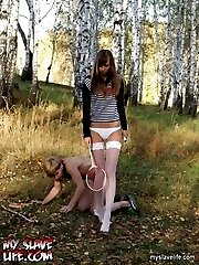 Young mistress in stockings torturing slave in the forest