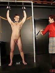 Madeleine Clavel has her feminine victim fellow strung up by his forearms and dog collar.  He is made to stand before her and take the lashing and various impact play that she inflicts on his figure.  She makes sure to get the bottoms of his feet, as she paddles them with a wooden spoon. The more he whines, the more she is amused.