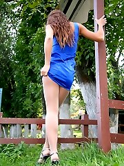 Feisty girl in a sexy blue dress and barely visible hose flashing outdoors