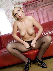 Sexy Scarlett in black mini on red leather sofa.
