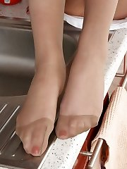 Nyloned feet are the best helper in the kitchen for long-legged brunette gal