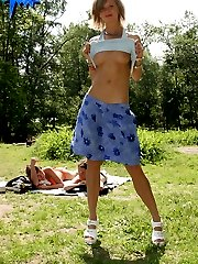 Blonde puss lifts her skirt on a crowded beach