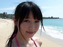 Vékony Ázsiai lány Tsukasa Arai sétál egy homokos tengerparton a nap alatt