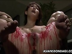 Chinese babe get her privates coated in wax.