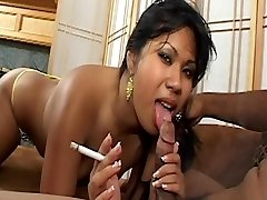 Asian honey with cute funbags smokes cigarette and gets jizz facial on couch