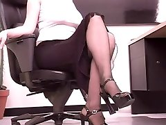 Busty dark haired secretary plays with a big fake penis at her desk