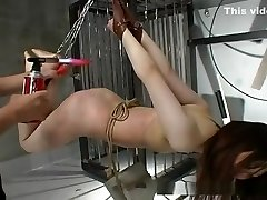 Brown haired Japanese gal suspended and teased with hot wax