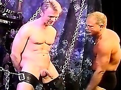 CBT blonde muscle stud is restrained and suspended as he gets his balls bashed.