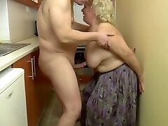 Insatiable, blonde grannie is toying with her tits and her lovers dick, in the kitchen