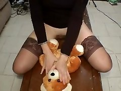 Gorgeous girl in pantyhose rides a otter bear on a table