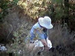 Smirking milf in big hat caught pissing outdoor