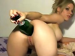 Insatiable blonde uses the big end of a bottle to stick in her ass
