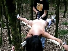 Tied to a cross and fucked with a immense fake penis in the forest
