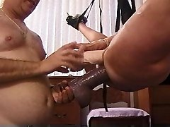 Mature Platinum-blonde slut in sling plunged with huge dildos