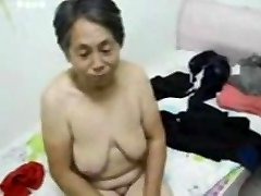 Asian Grandmother get dressed after romp