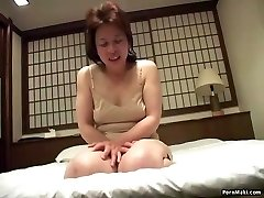 Asian grandma inserts a vibrator in her puss