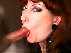 mature redhead dressed in red lipstick and sucking cock