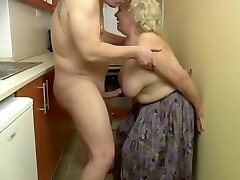 Insatiable, blonde granny is playing with her tits and her lovers prick, in the kitchen