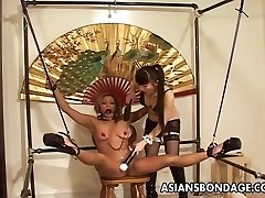 Restrained Asian woman tormented by her smoking hot mistress