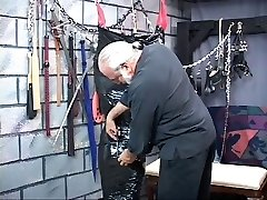 Chunky dark-haired bdsm slave gets packaged head-to-toe in black plastic