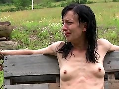 Anorexic brunette hussy gets her slim assets roped up to wooden fence outdoors