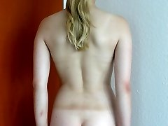 Naked blonde babe shows her well caned bottom - deep stripes