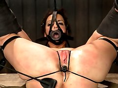 pBryn is bound on a wooden box in an open pile diver position. Her thighs are strapped open and...