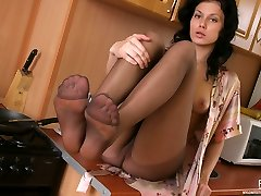 Curvy chick revealing her nyloned feet while sitting on the kitchen table