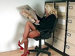 This sexy blonde looks great wearing her red heels in the office