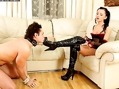 Seductive brunette mistress in black boots punishing her slave for being bad boy