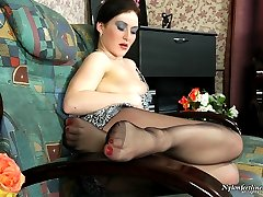 Nasty babe dangling her black high heel shoes and stroking her nyloned pink